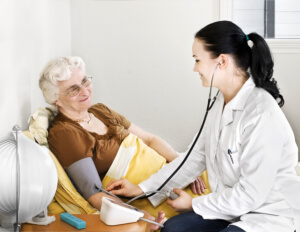 doctor checking the blood pressure of the senior woman